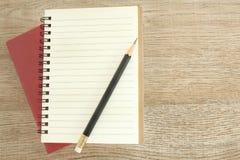 Ouvrez le carnet et le crayon sur la table en bois, foyer sélectif pour l'espace de copie image libre de droits