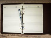 Ouvrez le carnet et le stylo sur le bureau en bois Photo libre de droits