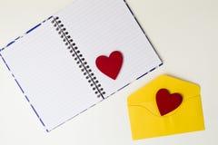 Ouvrez le carnet, l'enveloppe jaune et deux coeurs de feutre de rouge sur la table blanche Vue supérieure Copiez l'espace Images stock