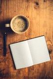 Ouvrez le carnet, le crayon et la tasse de café Images stock