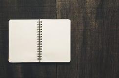 Ouvrez le carnet sur le bureau en bois noir la page vide préparent pour vos RP Image libre de droits