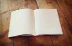 Ouvrez le carnet vide au-dessus de la table en bois préparez pour la maquette rétro image filtrée Photos libres de droits