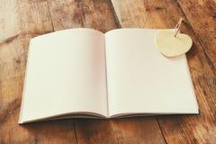 Ouvrez le carnet vide au-dessus de la table en bois préparez pour la maquette rétro image filtrée Photo stock