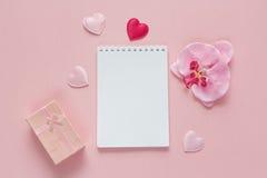 Ouvrez le carnet vide avec le boîte-cadeau, la fleur d'orchidée et les coeurs sur a Photographie stock