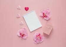Ouvrez le carnet vide avec le boîte-cadeau, les fleurs d'orchidée et les coeurs dessus Photographie stock libre de droits