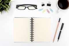 Ouvrez le carnet vide en spirale sur la table blanche de bureau Photos libres de droits