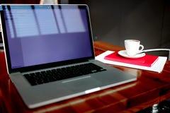 ouvrez le filet-livre et la tasse de café se trouvant avec le bloc-notes sur une table en bois dans un intérieur contemporain Images stock