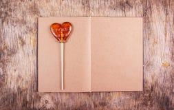 Ouvrez le journal intime avec les pages vides Amoureux sur un bâton Lucette sous forme de coeur Photographie stock