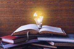 Ouvrez le livre avec des livres d'ampoule et de livre cartonné sur le fond en bois de mur Photos stock