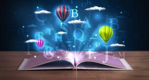 Ouvrez le livre avec les nuages et les ballons abstraits rougeoyants d'imagination Photographie stock