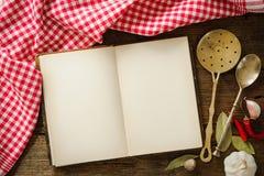 Ouvrez le livre de cuisine avec la vaisselle de cuisine image libre de droits
