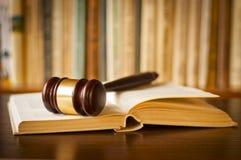 Ouvrez le livre de loi avec un marteau de juges Photographie stock libre de droits