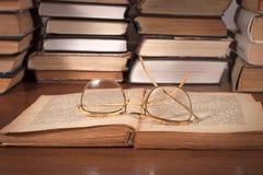 Ouvrez le livre sur la table et les verres Photo stock