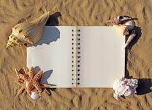 Ouvrez le livre sur le sable avec des Seashells l'ornant photos libres de droits