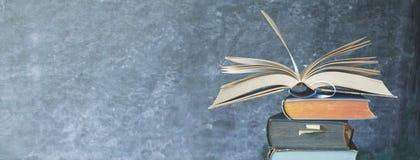 Ouvrez le livre sur une pile de vieux livres, tableau noir photographie stock
