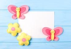 Ouvrez le papillon et les fleurs roses et jaunes avec le livre blanc, copyspace sur le fond en bois bleu Jouets fabriqués à la ma Photo stock