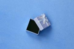 Ouvrez le petit boîte-cadeau dans le bleu avec de petits mensonges d'un arc sur une couverture de tissu bleu-clair mou et velu d' Photographie stock libre de droits
