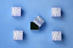Ouvrez le petit boîte-cadeau dans le bleu avec de petits mensonges d'un arc sur une couverture de tissu bleu-clair mou et velu d' Image libre de droits