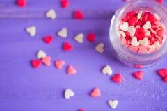 Ouvrez le pot en verre rempli de beaucoup de petites sucreries sous la forme de coeurs Image stock