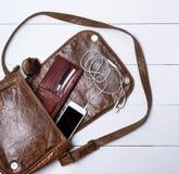 Ouvrez le sac en cuir brun femelle, un smartphone blanc Photo libre de droits