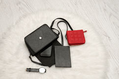 Ouvrez le sac noir avec les choses laissées tomber, le carnet, le téléphone portable, la montre et la bourse rouge La fourrure bl Images libres de droits