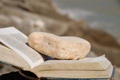 Ouvrez le vieux livre avec le signet en pierre sur les roches Photo libre de droits