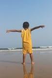 Ouvrez les bras Enfant exprès sa liberté à la plage de mer Photos stock