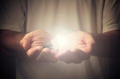 Ouvrez les mains avec l'ampoule photos stock