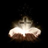 Ouvrez les mains retenant une croix Photographie stock