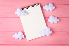 Ouvrez les nuages blancs avec le carnet, copyspace sur le fond en bois rose Jouets fabriqués à la main de feutre Ciel abstrait Photo stock