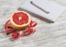 Ouvrez un bloc-notes vide, un pamplemousse et une bande de mesure sur une table en bois légère image stock