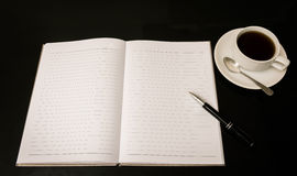 Ouvrez un carnet, un stylo et une tasse de café blancs vides Photographie stock