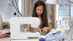 Ouvrière couturière au travail dans des vêtements de couture d'atelier sur la machine à coudre banque de vidéos