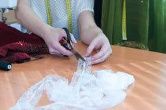 Ouvrière couturière coupant la dentelle avec des ciseaux sur le studio de couture de table en bois photos stock