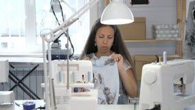 Ouvrière couturière cousant dans l'atelier d'atelier sur des bords de tissu d'overlock, plan rapproché de mains clips vidéos