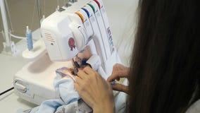 Ouvrière couturière cousant dans l'atelier d'atelier sur des bords de tissu d'overlock, plan rapproché de mains banque de vidéos