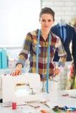 Ouvrière couturière heureuse dans le studio près du sewingmachine Images libres de droits