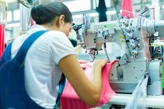 Ouvrière couturière indonésienne dans l'usine asiatique de textile photos stock