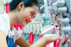 Ouvrière couturière indonésienne dans l'usine asiatique de textile Image libre de droits