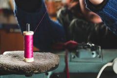 Ouvrière couturière mettant le fil dans la machine à coudre Photo libre de droits