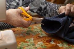 Ouvrière couturière qui coupe le tissu images libres de droits