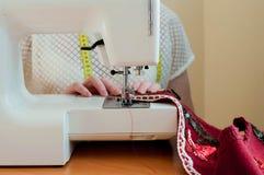 Ouvrière couturière s'asseyant à la machine à coudre et travaillant dans le studio de couture photos stock