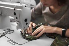 Ouvrière couturière travaillant à la machine à coudre électrique moderne faisant les vêtements exclusifs dans le studio de mode image stock