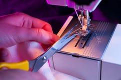 Ouvrière couturier coupant un amorçage après la couture Photos libres de droits