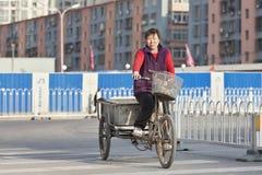 Ouvrière de femme migrante sur un vélo de fret, Pékin, Chine Photo libre de droits