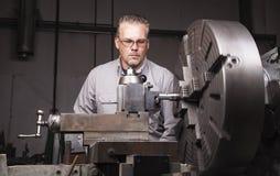 Ouvrier à l'aide du tour en métal images stock