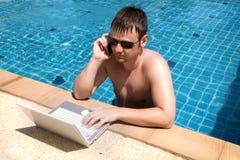 Ouvrier avec l'ordinateur portable dans la piscine image libre de droits