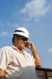 Ouvrier avec le casque antichoc au téléphone Images stock