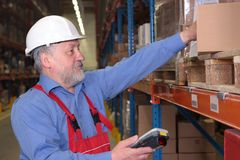 Ouvrier aîné avec le lecteur de code à barres Image libre de droits