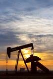 Ouvrier chargé des pompes d'huile à l'image de verticale de lever de soleil Images stock